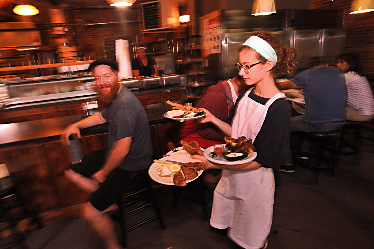 Five Points Bakery owner Kevin Gardner gives his daughter, Molly, a smile as she carries out an order at the popular Westside eatery.