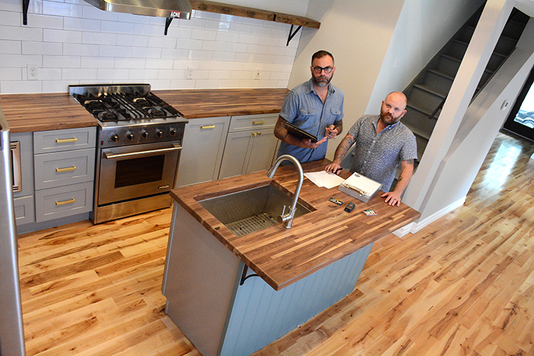 Acme Cabinet owners Keith Szczygiel and Sean Wrafter stand in the kitchen of a West Side home they gutted and refitted with their custom cabinetry.