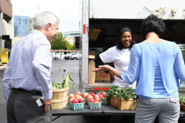 Allison Dehonney of Urban Fruits & Veggies talks with Bruce  Morlok, a temporary Blue Cross Blue Shield worker, and Janene  Kosnikowski, a Blue Cross Blue Shield employee resources employee,  during her pop-up market at BCBS on Sept. 9, 2017.