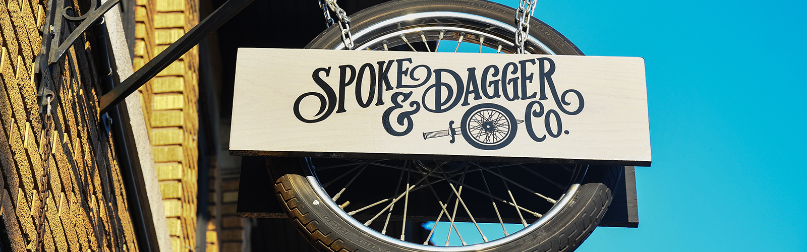 Spoke & Dagger Co., located at 1434 Hertel Ave., Buffalo, is identifiable by its swinging tire sign. <span class=&apos;image-credits&apos;>Jessica Brant</span>
