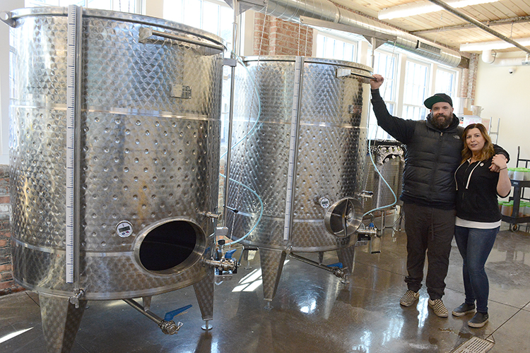 The Marvins stand near the large cooking vats in their facility. Barrel + Brine specializes in pickled and fermented foods.