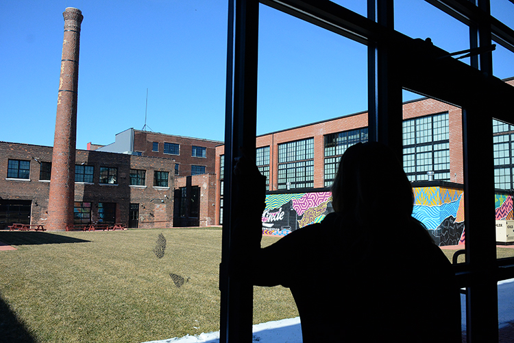 Lindsey Marvin looks out on the courtyard of the building where Barrel + Brine is operated. A summer event is being planned by the businesses in the complex.