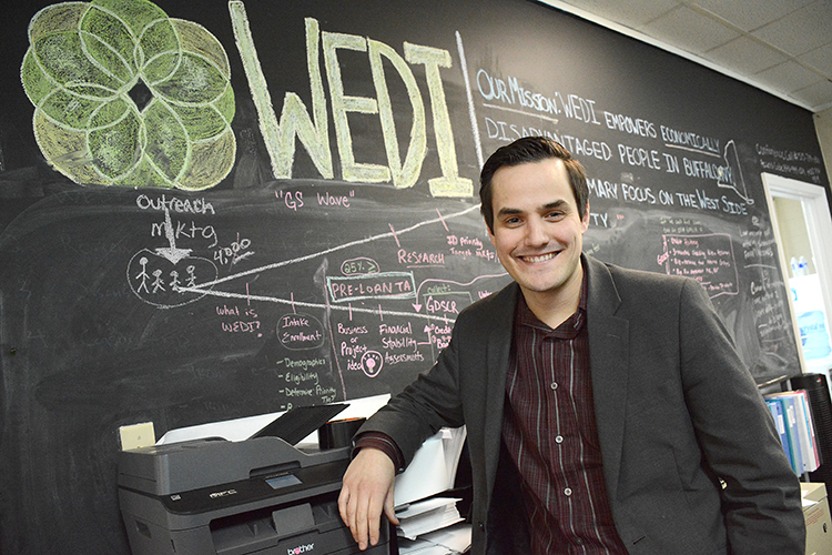 "Benjamin Bissel, executive director of the Westminster Economic Development Initiative, stands in front of the ""mission board"" in his Grant Street headquarters."
