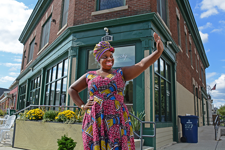 Phylicia Dove, owner of Black Monarchy, waves to a friend in front of her West Side store at 527 West Utica St. on Buffalo's West Side.