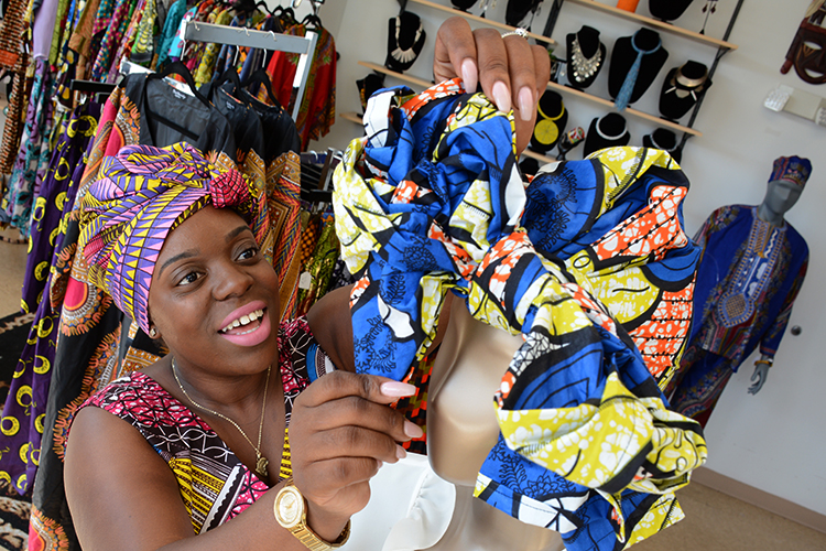 Phylicia Dove ties a traditional African head wrap at her West Side store.