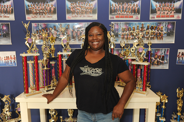 Ayanna Williams, founder and owner of Buffalo All-Star Extreme, 1245 Main St., Buffalo, stands in front of a wall of trophies and photos of the teams that won them.