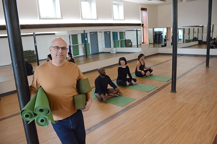 Flanked by yoga students, Evolation Yoga owner David Drost stands in his studio on Buffalo's West Side.