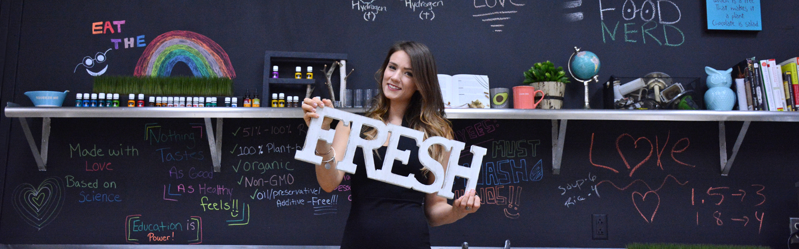 Sharon Cryan, founder and owner of Food Nerd, stands in front of her inspiration board holding an adjective that sums up her product. <span class='image-credits'>Dan Cappellazzo</span>