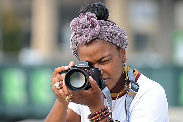Aitina Fareed-Cooke, a CEPA Gallery Award-winning photographer and owner of Get Fokus'd Productions, shoots with her Sony mirrorless digital camera at Canalside.