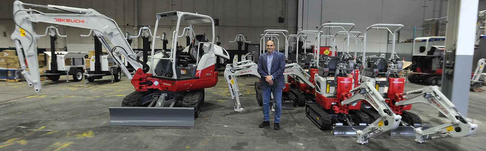 Green Machine CEO Jon Williams with a fleet of Takeuchi excavators that will be retrofitted with Green Machine batteries, which provide clean power and can run for seven hours before needing a recharge. <span class='image-credits'>Dan Cappellazzo</span>
