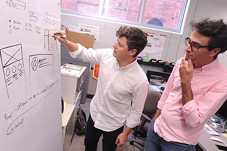 Helm founders Nicholas Barone and Jonathan Gorczyca use their idea board as they discuss their latest project.