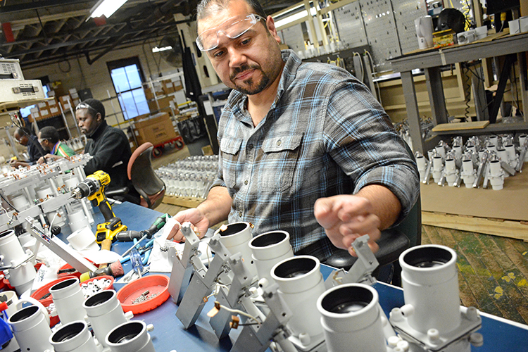 Litelab employee Ahmed Al Abboodi, who came to Buffalo from Iraq four and half years ago, assembles AO4 projector light fixtures at the downtown Buffalo facility.