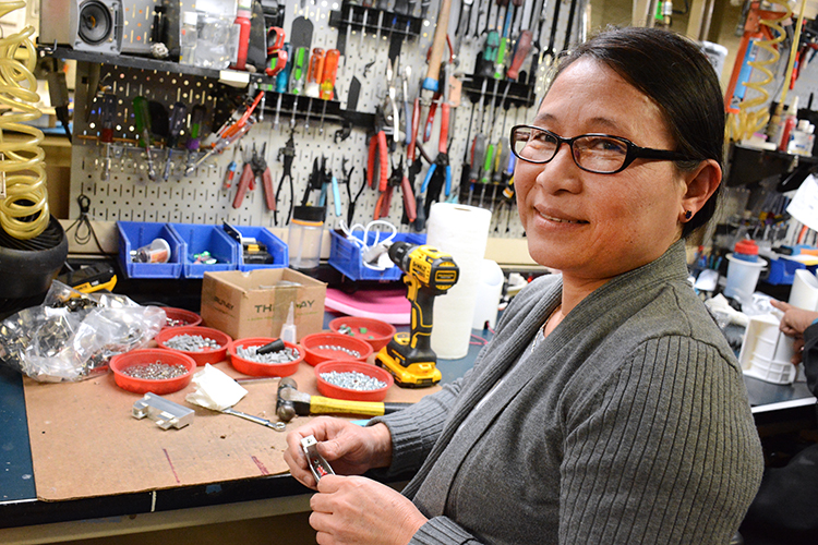 Litelab employee Julia Bu, formerly of Myanmar, assembles a light fitting at the downtown Buffalo facility.