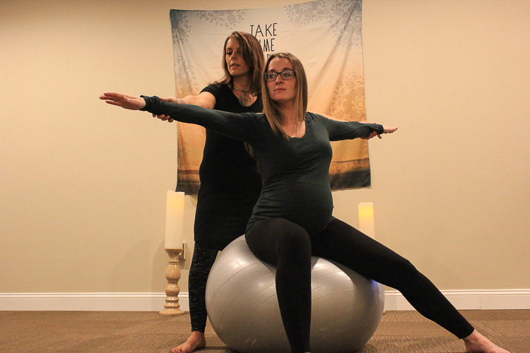 Yoga Instructor Molly McDermott and a client, Emily More in the Warrior 2 pose.