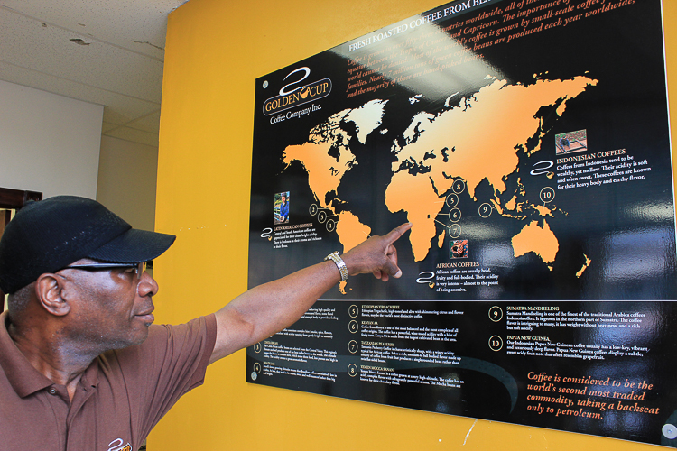 Larry Stitts with a map of the various countries where Golden Cup Coffee imports their coffee.