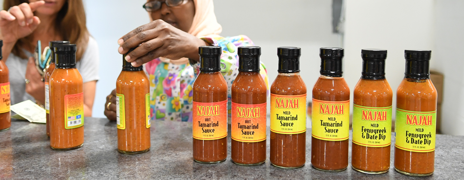 The Najah savory sauce line: owner Bisharo Ali shows product to a new customer  <span class='image-credits'>Nancy J. Parisi</span>