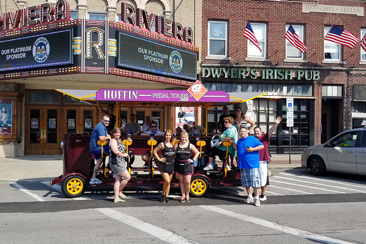 Happy peddlers stop on Webster Street in North Tonawanda in front of the Riviera Theatre, which is listed on the National and New York State Register of Historic Places, and Dwyer's Irish Pub.