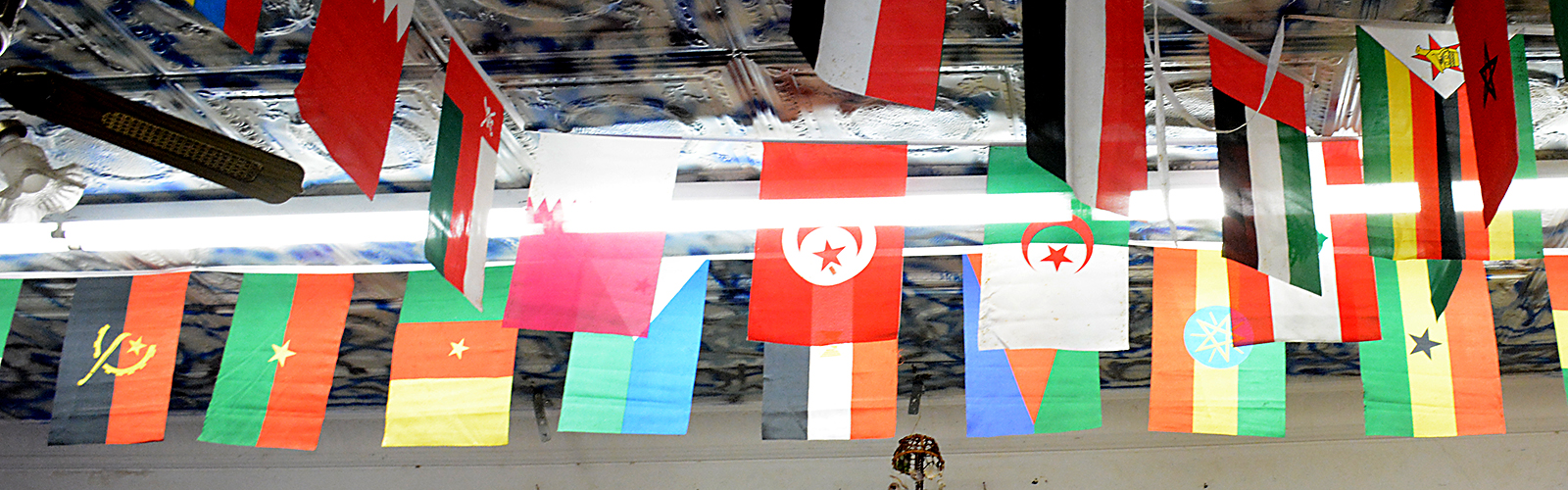 International flags displayed on the ceiling of Yasin Market.