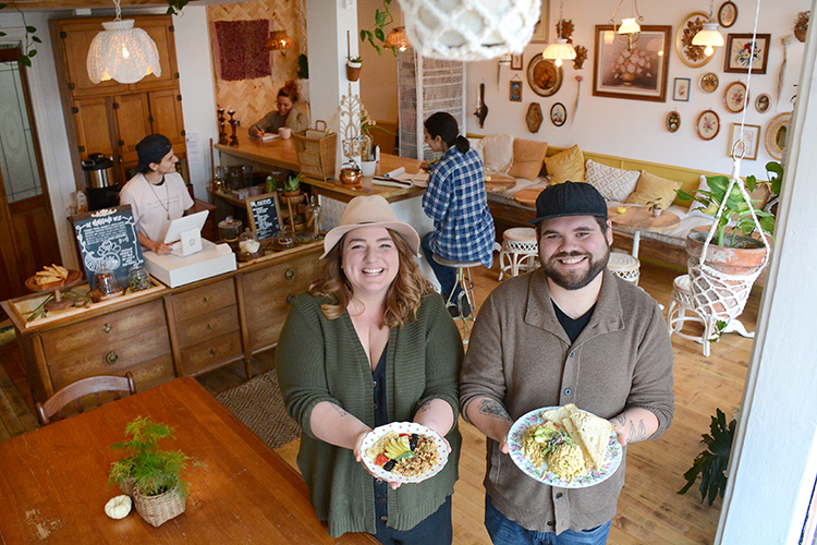 "Root & Bloom owners Sarah and James Sendlbeck hold two of their dishes: the ""Ruby,"" house-cultured cashew yogurt with homemade granola and seasonal fruit with apple honey; and the ""Nelson,"" eggless scramble with house-cultured queso and local bread."
