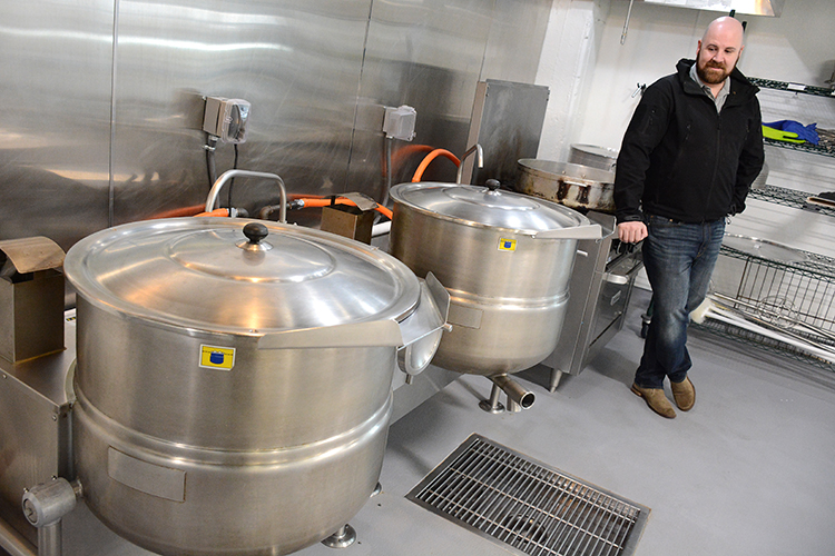 Zack Schneider, co-owner of Ru's Pierogi, stands next to giant cooker vats at his Niagara Street restaurant and manufacturing facility.
