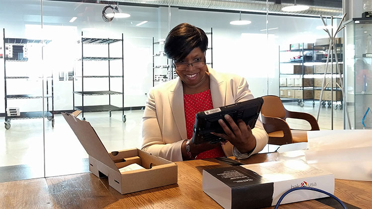 Sandra Ann Talley, winner of the UpstartNY sweepstakes, unboxing her new Bak USA Seal Tablet at Bak's Buffalo headquarters.  Photo by LaunchNY.