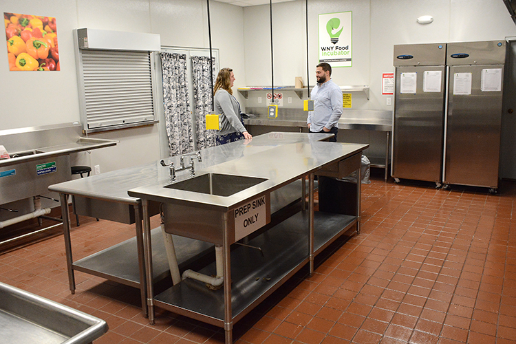 Amanda Henning talks to Marc Ducharme, Cornell Cooperative Extension public relations and marketing coordinator, in the WNY Food Incubator, a NYS certified kitchen that can be used by area chefs.